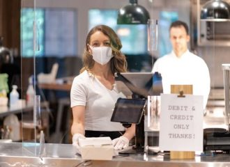 woman wearing mask accepting cashless payment